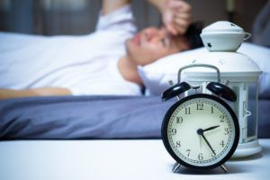 man sleeping in bed with clock on nightstand