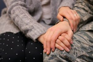 hands of wife holding hands of military spouse
