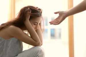 Hand reaching towards a depressed woman at home
