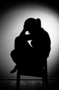 Silhouette of a woman curled up on a chair